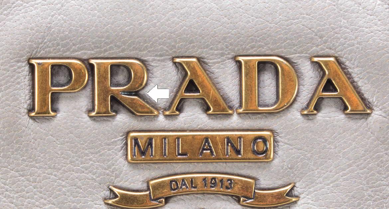 Буква R на треугольной бирке сумки PRADA